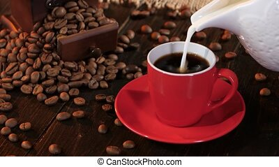 In little red cup of espresso poured milk or cream, pouring...