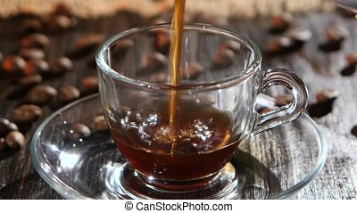 Black coffee is poured into glass transparent cup on saucer...