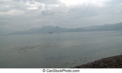 Lake in mountains against sky and mist over water in...