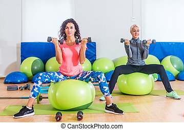 Fitness women exercising sitting on green Swiss balls doing...