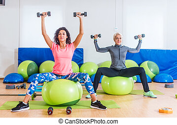 Sporty women training indoors doing exercise sitting on...