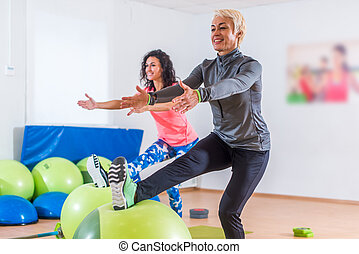 Group of active cheerful sporty women doing single leg...