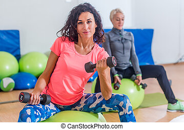 Smiling slim Caucasian women doing exercises with fitness...