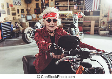 Outgoing grandmother driving motorcycle in mechanic shop -...