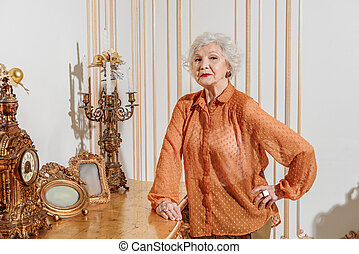 Confident old woman posing near chic table - I am proud of...