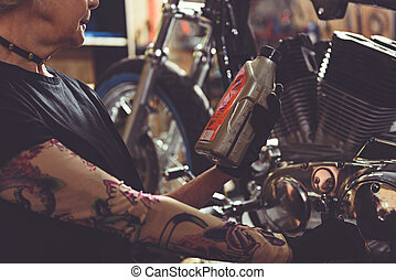 Female pensioner wishing to lubricate motorcycle - Old woman...