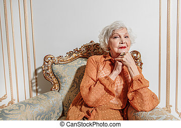 Pensive mature lady relaxing on expensive chair - Dreamful...