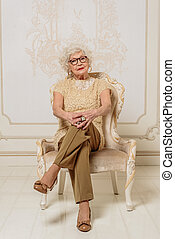 Serious mature lady having a seat - Smart old woman is...
