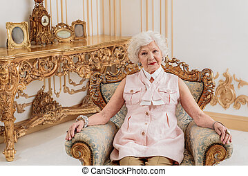 Serious old lady sitting on luxury armchair - Sophisticated...