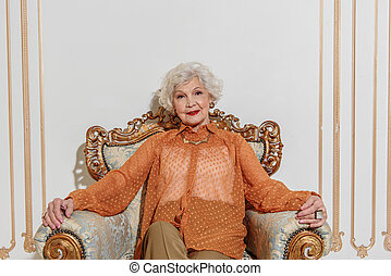 Happy old woman sitting on armchair - Richness is great....