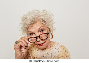 Severe old woman gazing at camera - I see you. Serious...