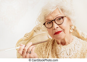 Serious old woman smoking cigarette - Elegant mature lady is...
