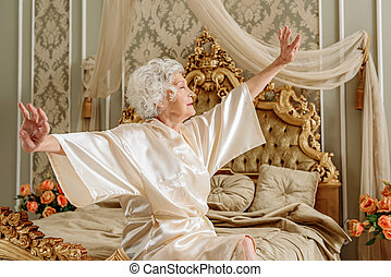 Serene old lady waking up in morning