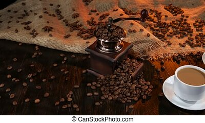 Two cups with latte on table strewn with coffee beans, mugs...