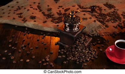 Coffee grinder full of coffee beans and cup of espresso -...