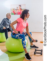 Sporty slim women taking part in gym fitness class...