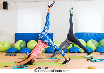 Slim fit women practicing yoga indoors in fitness studio. Two athletic females standing in One-Legged Downward Facing Dog pose stretching the entire body