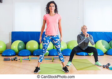 Group of fit women exercising doing squatting exercises...