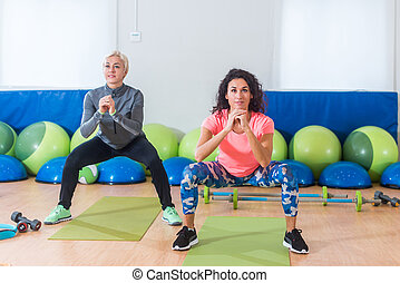 Two women in sportswear doing bodyweight squats while...