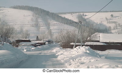 Beautiful mountain village in winter day, traditional house and car road covered by heavy snow