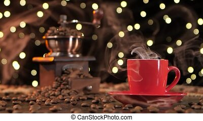 Red cup of hot coffee with smoke and coffee grinder - Red...