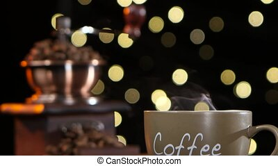 Cup of hot coffee with a smoke and coffee grinder - Cup of...