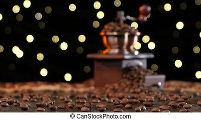 Grinder filled with coffee beans and cup on a saucer -...