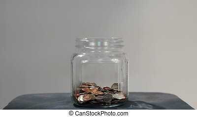 Money Falling In Jar - Money falls into a clear jar from...