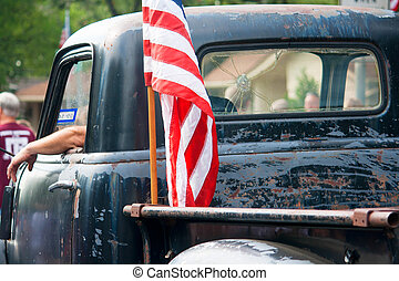 American Flag on Old Pickup Truck at Fourth of July Parade -...