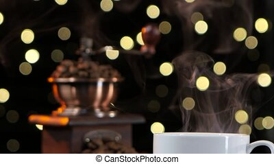 Closeup smoke with a white cup. Coffee mill with beans -...