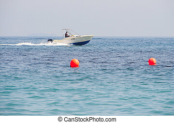 Powerboat - white boat and orange floats in the blue sea...