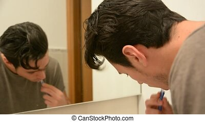 Headshot of attractive young man brushing teeth with...