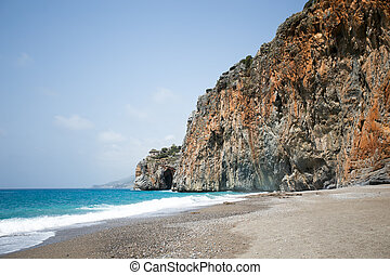Mediterranean beach with turqouise sea and rocks on shore -...