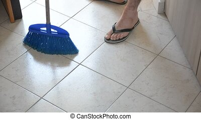 Young Man with Broom Sweeping the Floor - Young Handsome Man...