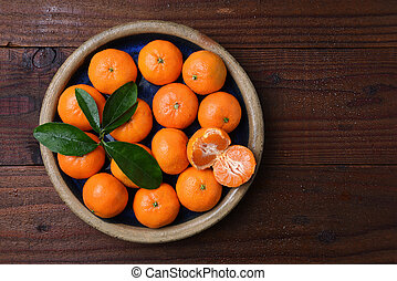 Mandarin Oranges in Bowl on Wood - Top view of a plate of...
