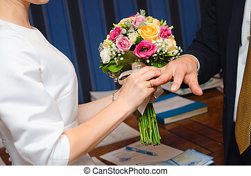 Newlyweds exchange rings, groom puts the ring on the bride's...