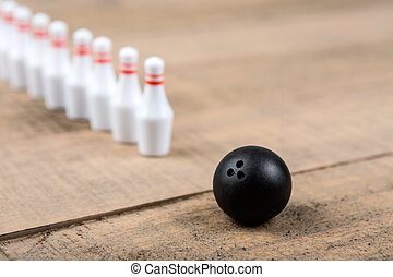 Toy bowling ball and pins isolated on a wood background