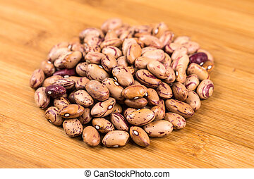 Organic cranberry beans isolated on a wood background