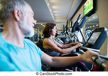 Beautiful fit senior couple in gym doing cardio work out. -...