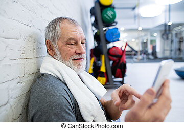 Fit senior man in gym resting, holding smart phone. - Fit...