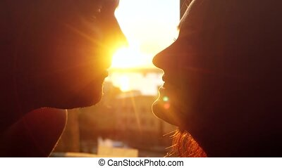 Romantic young couple is kissing looking each other on a sunset with sun shining bright behind them on a horizon with lense flare effects. First kiss of young love.