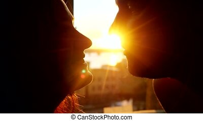 Romantic young couple silhouette is kissing looking each other on a sunset with sun shining bright behind them on a horizon with lense flare effects.