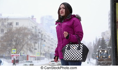 A girl stands at the bus stop in winter, she's waiting for...