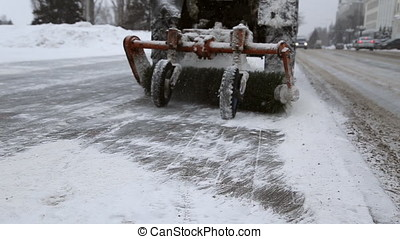 A tractor removes snow from the sidewalk