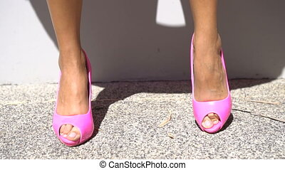 Pink high heel shoes - Closeup front view of female legs in...
