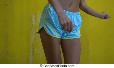 Woman in yellow bra and blue sporty shorts
