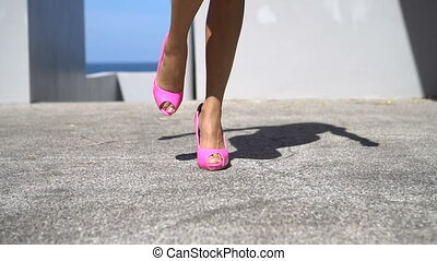 Pink high heel shoes - Closeup front view of female legs...