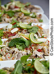 Spicy pork salad with dried chili and garnished with mint. -...