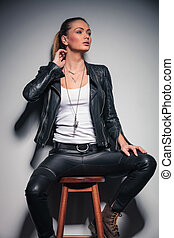 woman in leather clothes with one hand behind her neck
