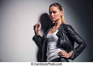 beautiful woman in leather clothes leaning on grey wall and...